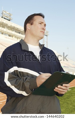 Coach with clipboard standing by running track - stock photo