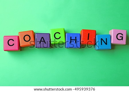 Coaching concept. Wooden cubes on green background