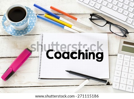Coaching word with cup of coffee. Coaching word Written on white paper with cup of coffee ,keyboard , calculator,glasses, felt pens on wooden background - stock photo