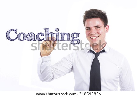 Coaching - Young smiling businessman writing on transparent surface - stock photo