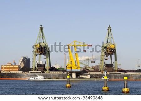coal cranes in the harbor of rotterdam - stock photo