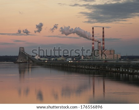 Coal fired power plant at river's edge at dusk - stock photo