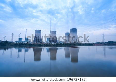 coal-fired power plant, cooling towers and river in cloudy