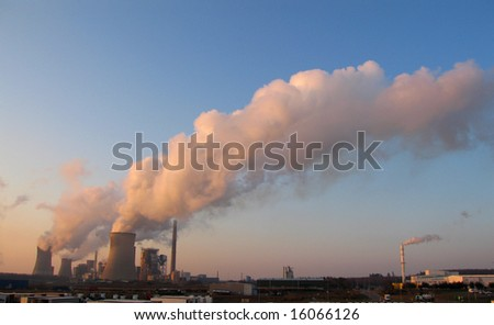 Coal fired power plants generating smoke at the sunset - stock photo