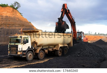 Coal loading at open mining site - stock photo