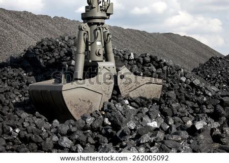 Coal loading excavator, heaps of coal - stock photo