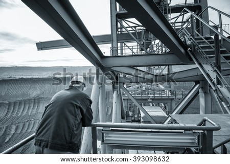 Coal mine worker with a helmet on his head standing in front of huge drill machine and looking at it. Rear view. Monochromatic toned image. - stock photo