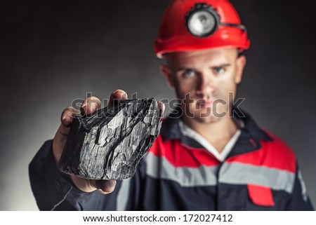 Coal miner showing lump of coal against a dark background - stock photo