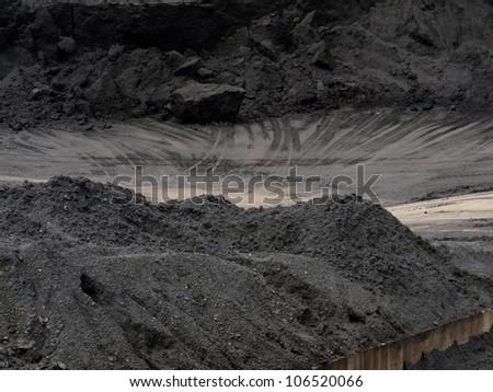 Coal piled to heaps on coal mine train transfer storage site - stock photo