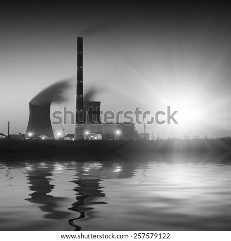 Coal power plant with rising sun, reflected in water. Monochrome colors - stock photo