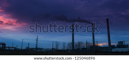 Coal powered plant and smoke stacks under dramatic evening sky