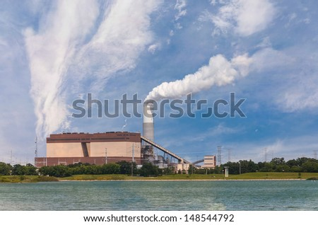 Coal powered power plant on bank of a river spewing pollution in the air, with natural gas generators as backup - stock photo
