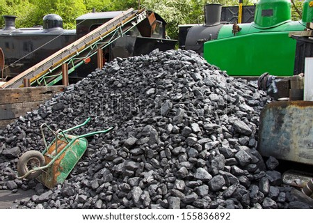 Coal stacked trackside alongside two vintage steam engines on the renovated rail line between Bristol and Bath at Bitton station UK - stock photo
