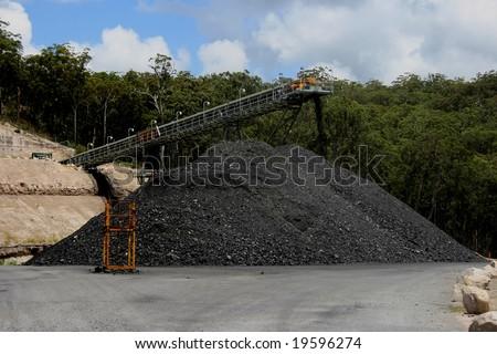 Coal stockpile and conveyor belt - stock photo