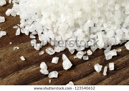 Coarse salt on a old wooden table, closeup - stock photo