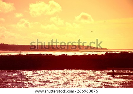 Coast and nature. Sunset over sea with jetty bathed in the sun rays. - stock photo