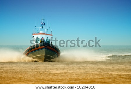 coast guard full speed towards the beach - stock photo