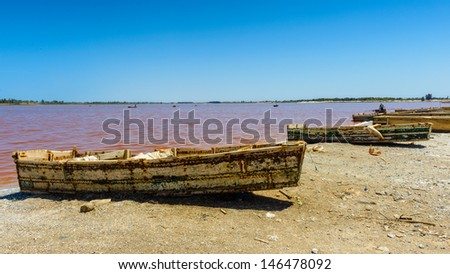Coast of a pink water lake in Senegal with boat on it - stock photo