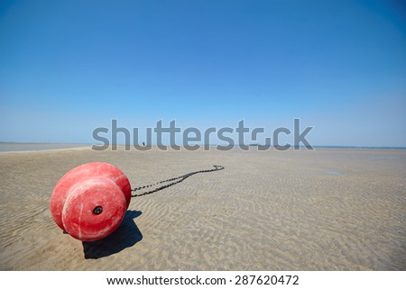 Coast Sea. Summer . At low tide . Sunny day. Clear sea, the fresh breeze . Red buoy in the sand . Walking along the seashore . Clear blue sky. White warm sand . The low horizon line . - stock photo