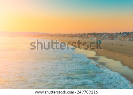 Coastal cityscape during sunset with clear sky, vibrant colors - stock photo