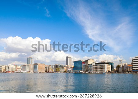 Coastal cityscape with modern buildings under cloudy sky. Izmir city, Turkey - stock photo
