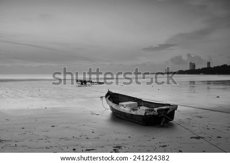 Coastal fishing boats moored at the seaside. With sunset light black and white tones.
