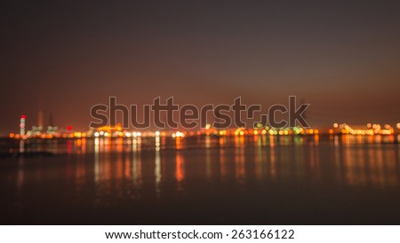 Coastal industrial city in night time - stock photo