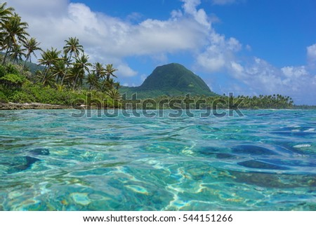 Coastal landscape of Huahine island, islet with coconut trees and the mount Moua Tapu seen from the lagoon, south Pacific ocean, French Polynesia