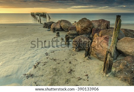 Coastal landscape with old broken fishery wharf, Baltic Sea. Image slightly toned for inspiration of retro style - stock photo
