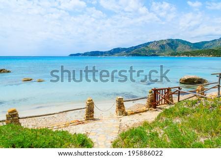 Coastal path along emerald green sea water and rocks on coast of Sardinia island near Spiaggia del Riso beach, Italy - stock photo