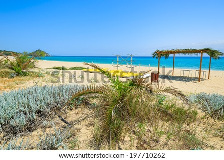 Coastal promenade with palm trees along a Cala Sinzias beach and turquoise sea water, Sardinia island, Italy  - stock photo