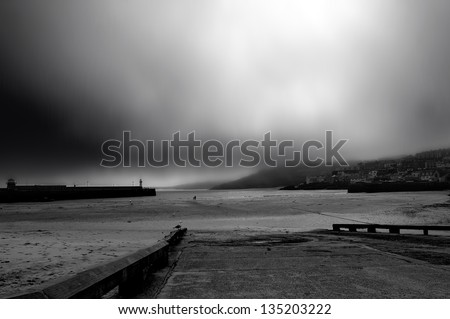 Coastal scene with man and child watching the storm approaching - stock photo
