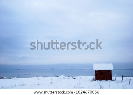 Coastal snowscape with an old fishing cabin by the coast of the swedish island Oland in the Baltic Sea