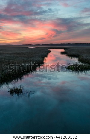 Coastal Wetlands with Dramatic Sunrise - stock photo