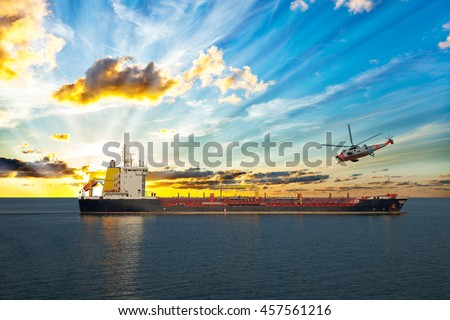 Coastguard rescue helicopter is approaching the ship. - stock photo