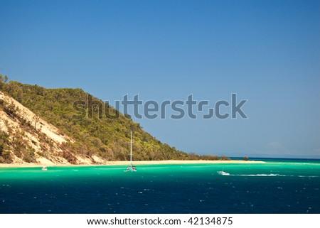 Coastline and sailboat on Moreton Island - stock photo