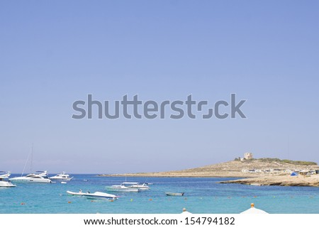 Coastline in Malta with blue sea, blue sky and power boats. Space for text - stock photo