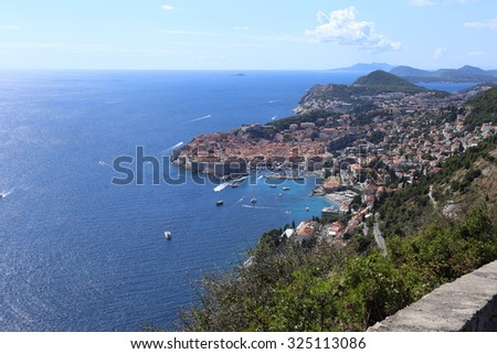 Coastline of Croatia with Dubrovnik and its harbour the main focus. Small boats scatter the sea along the coast. - stock photo