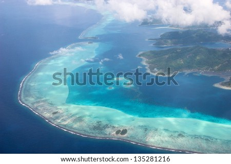 Coastline of Tahaa, French Polynesia, surrounded by coral reefs - stock photo
