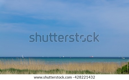 Coastline of the Baltic Sea with sail ships in the Background, Germany - stock photo