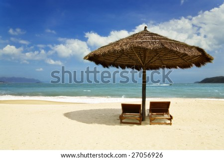 coastline of tropical sand beach with parasol and wooden chairs
