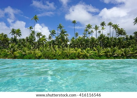 Coastline with coconut trees and turquoise water of an islet of Huahine, seen from water surface, Pacific ocean, French Polynesia - stock photo