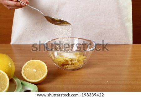 Coating lemon peels with sugar. Candied Lemon Zest Cooking. Series. - stock photo