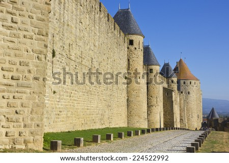Cobble stone path on a surrounding medieval fortress wall. Beautiful castle with towers on a sunny day.