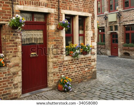 Cobbled lane with flowers at the district of Beguinage, Ghent, Belgium