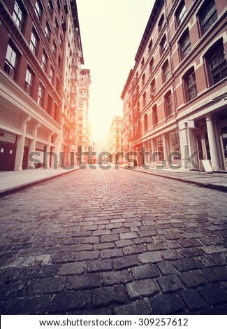 Cobbled Soho street in New York with added sun effect and Instagram filter - stock photo