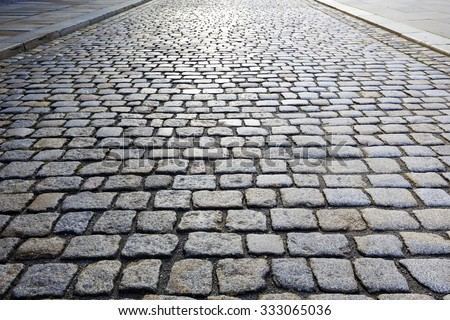 Cobbled stone road shown at a small angle, reflection of light seen on the road - stock photo
