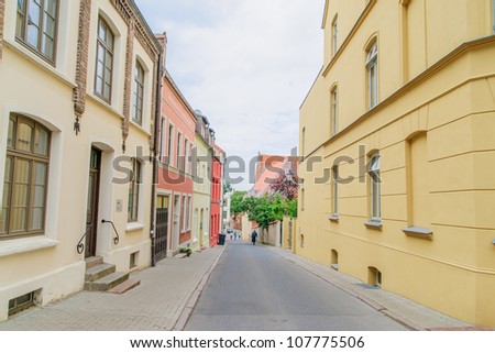 Cobbled street in historic Wismar, a Hanseatic League town in Northern Germany on the Baltic Sea, with elegant building styles from 14th-century Gothic to 19th-century Romanesque revival. - stock photo