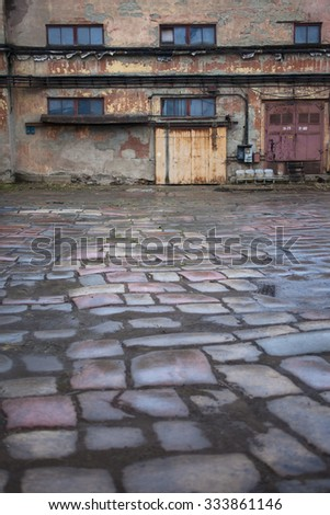 cobblestone and wall of old factory, industrial background - stock photo