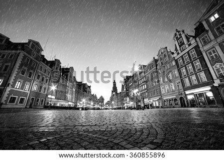 Cobblestone historic old town in rain. The market square at night. Wroclaw, Poland in black and white. Perfect empty space to put your object on the ground. - stock photo